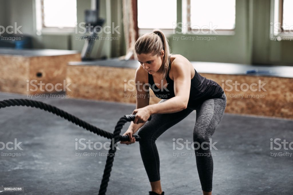 Young woman working out with ropes at the gym stock photo