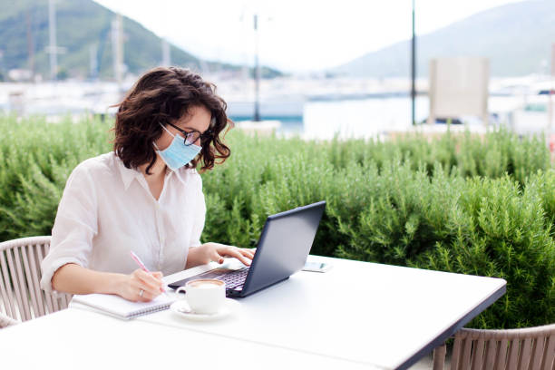 Young woman working safety in empty cafe outdoors. Social distancing during quarantine. Freelancer stock photo