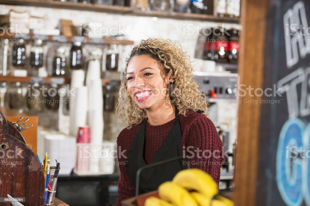 Young woman working the cash register at coffee shop stock photo