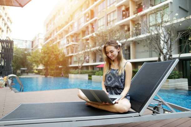 young woman working uses new laptop pc outdoors remotely as freelancer close to swimming pool and apartment building - competition group stock photos and pictures