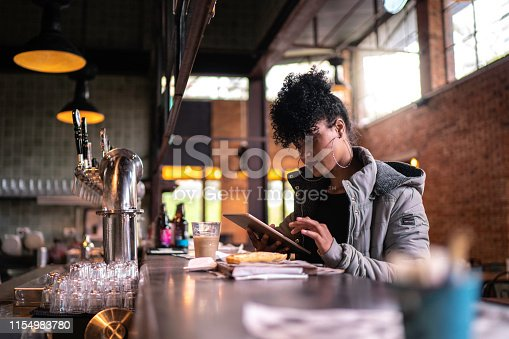 Young woman working using digital device in coffee shop