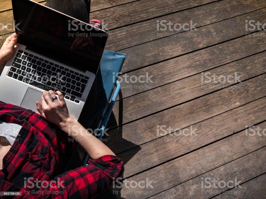 Junge Frau sitzt auf einem Hof mit ihrem Laptop arbeiten – Foto