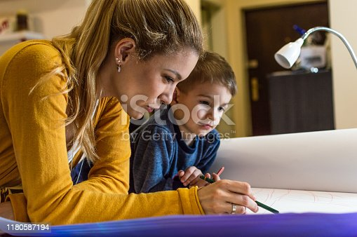 Young woman working late in her home office. Boy is with her. They are drawing with a ruler on a blueprint. Copy space.