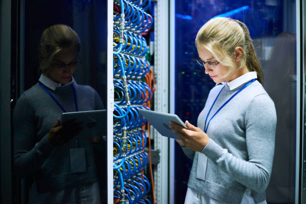 young woman working with supercomputer - women in tech stock photos and pictures