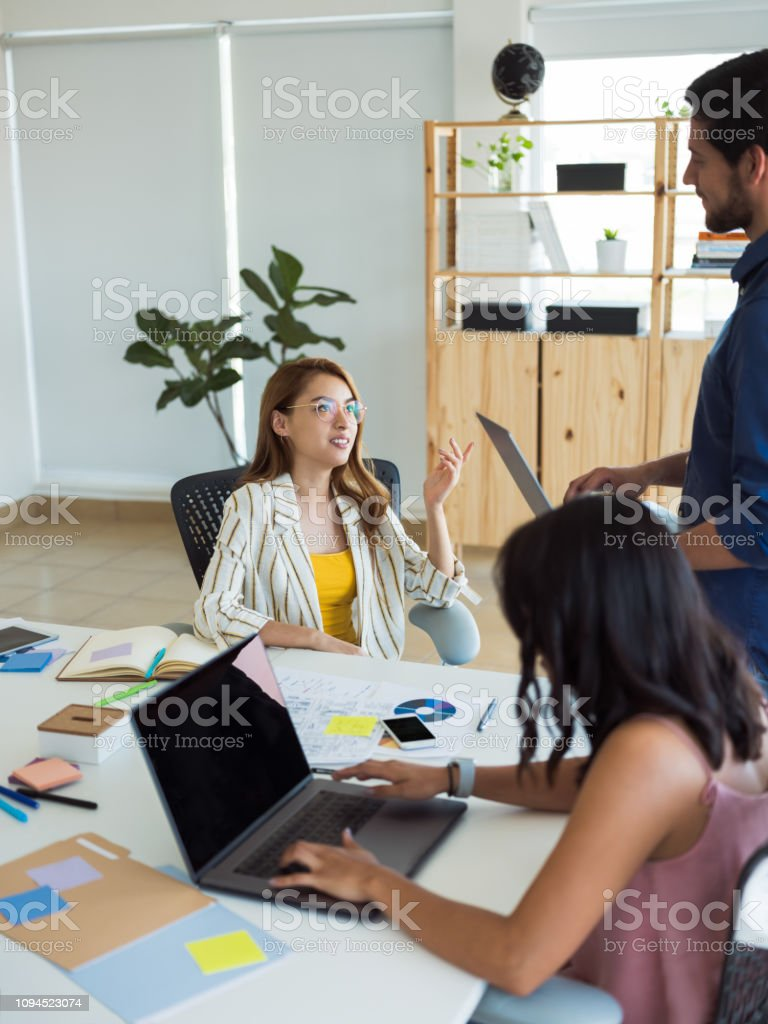Young woman working with teammates in the office stock photo