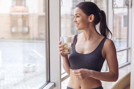 Young female training in gym healthy lifestyle drinking water