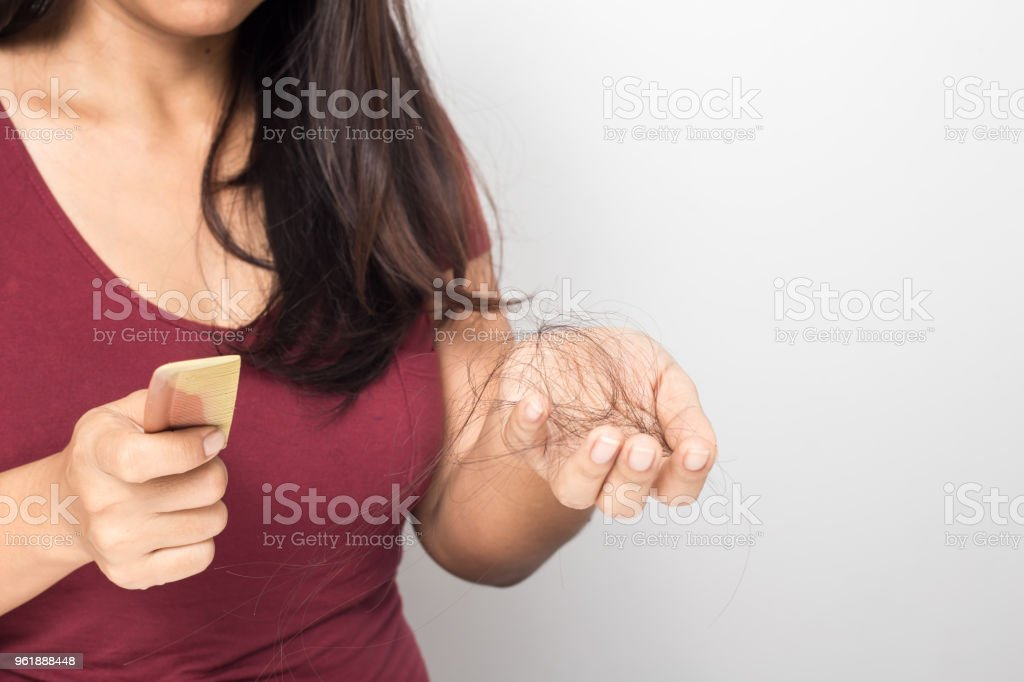 young woman worried about hair loss on a white background stock photo