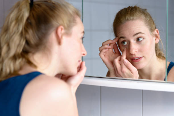 Young woman worried while looking in the mirror Over the shoulder view of a beautiful young woman worried about aging while looking in the mirror at the skin around her eyes auk stock pictures, royalty-free photos & images