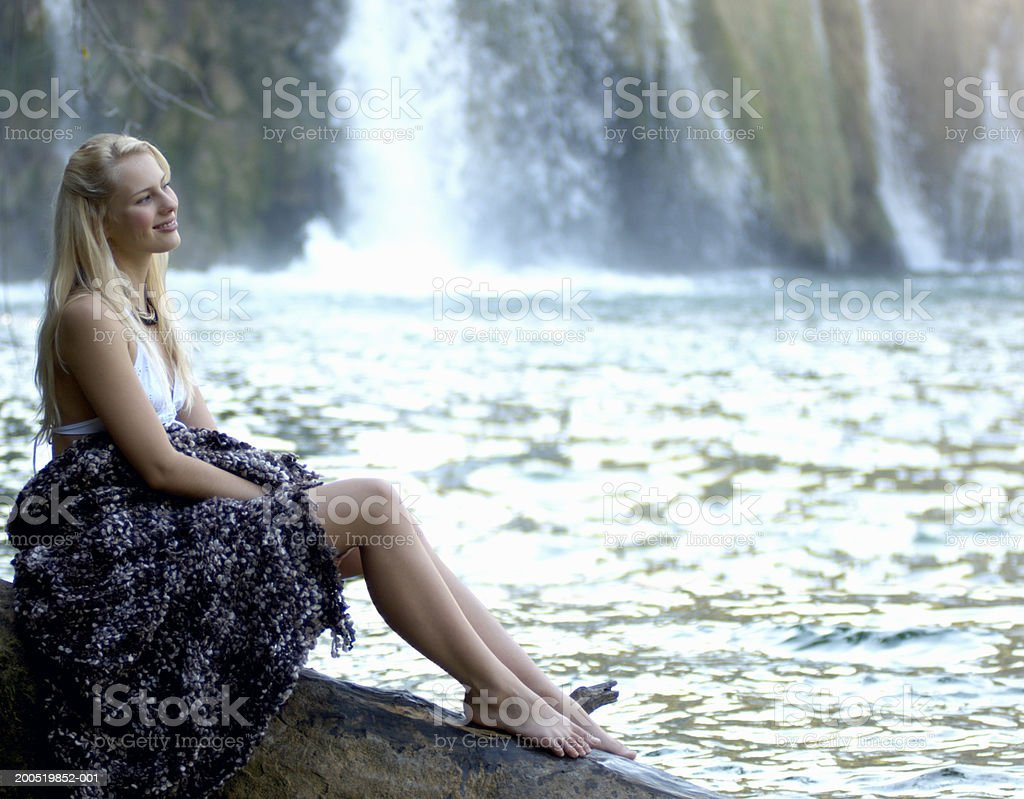 Young woman wrapped in blanket, sitting on rock near waterfall royalty-free stock photo