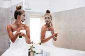 Young woman wrapped in towel applying facepack. Beautiful female in front of mirror applying facial mask.
