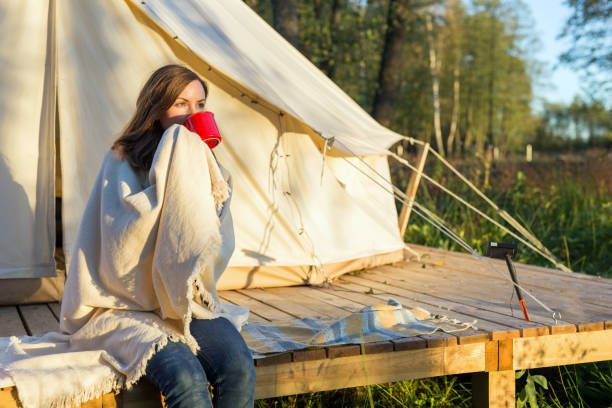 Young woman wraps blanket over herself while drinking coffee near canvas tent in the morning stock photo