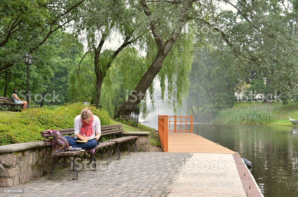 Young woman write something in her notebook on river bank stock photo