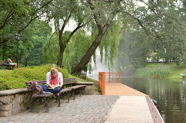 Mujer joven escribir algo en su computadora portátil en la orilla del río - foto de stock