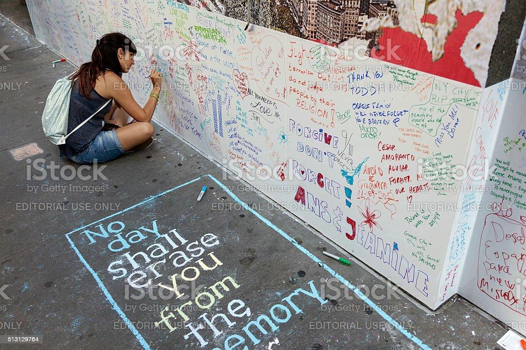young woman writes on wall near ground zero stock photo