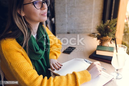 1183295518 istock photo Young woman writing a story in a cafe 1129203346