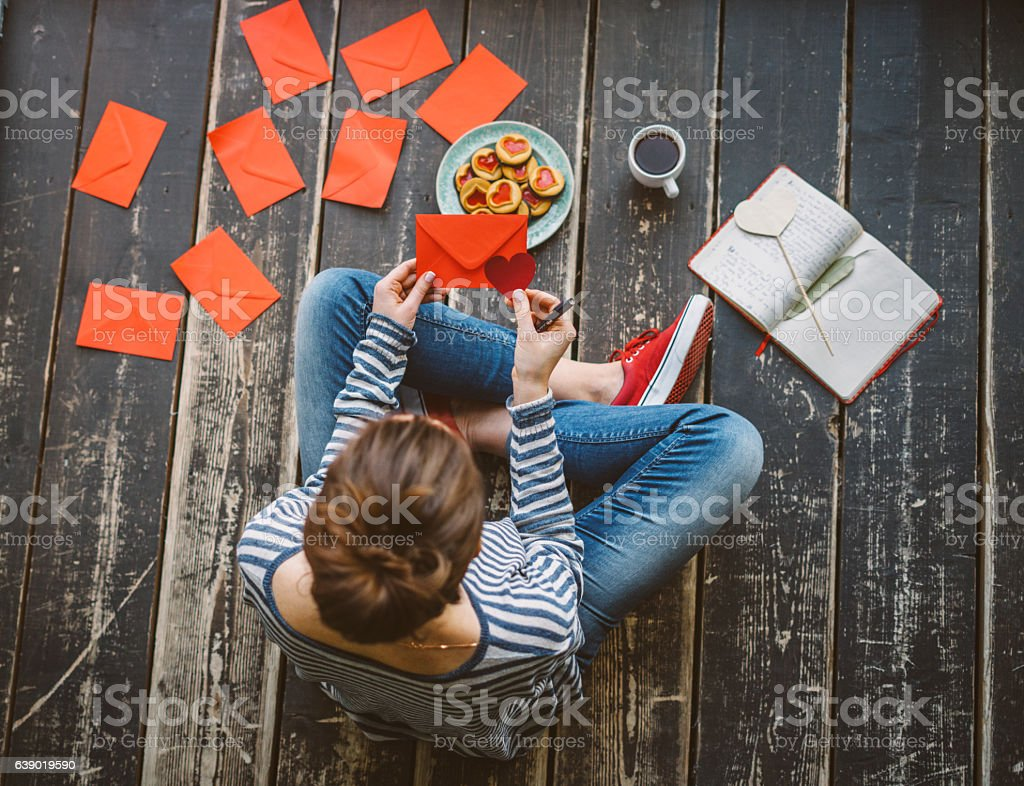 Young woman writing a valentine card - top view stock photo