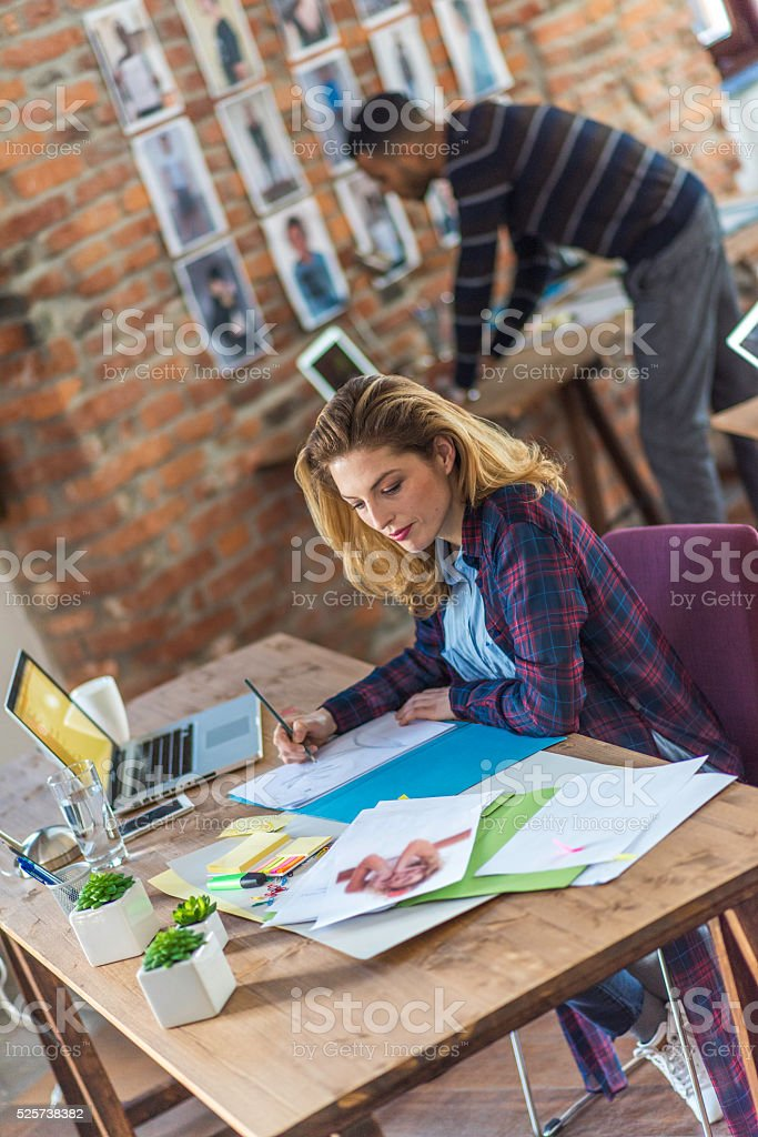 Young woman writing and using laptop in the office stock photo