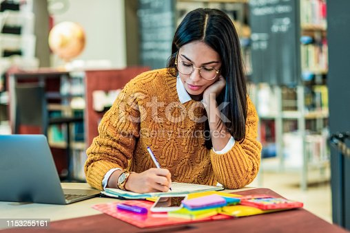 istock young woman writing and working on a project 1153255161