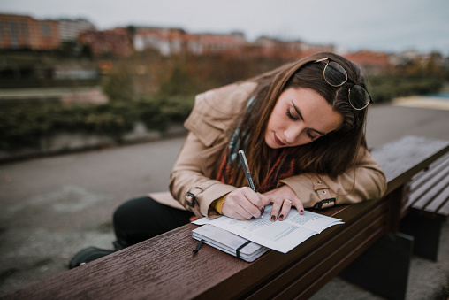 A young woman sitting on a public park bench and writing
