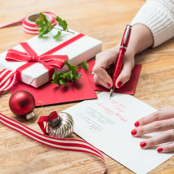 young woman writing christmas cards with red nails, a red pen, and holiday decorations stock photo
