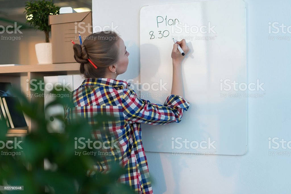 Young woman writing day plan on white board, holding marker stock photo