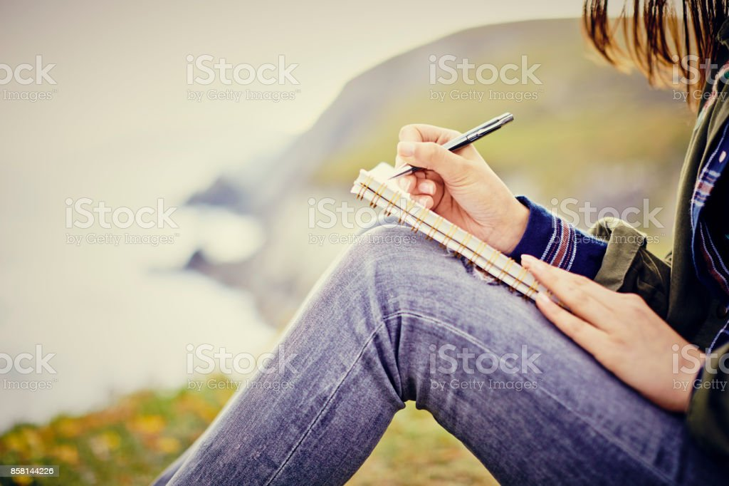 Young woman writing in diary while sitting on mountain stock photo