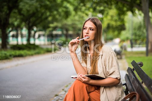 Young woman writing in her diary and contemplating outdoors.