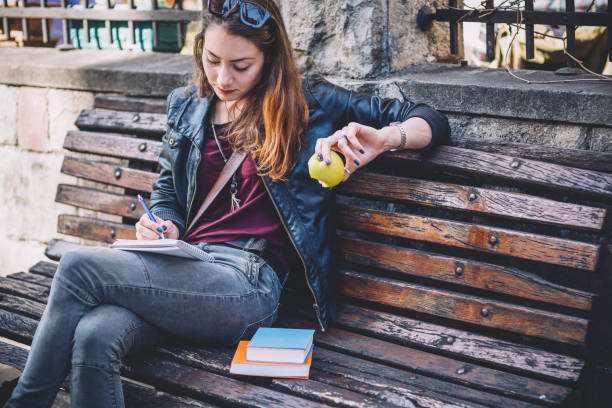 Young woman writing in her journal and eating apple while sitting on the bench outdoors stock photo