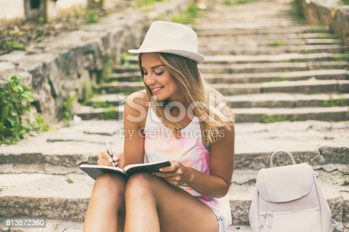 istock Young woman  writing in her notebook 813872360