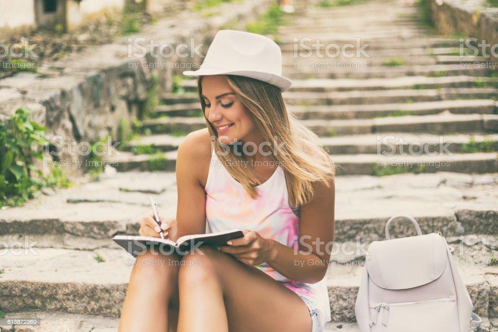 Mulher jovem, escrevendo no caderno dela - foto de acervo