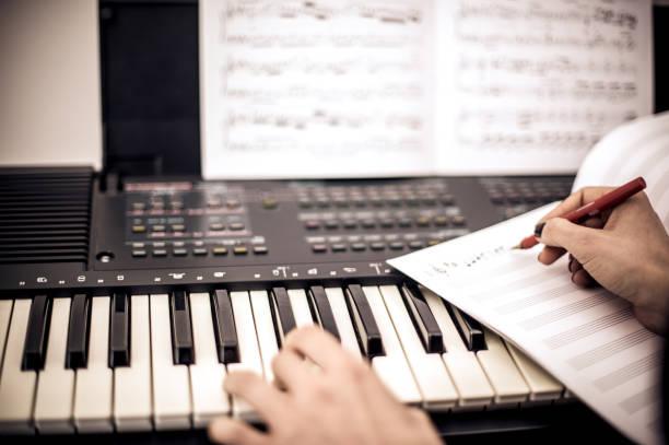 junge frau, die musikalische note während des spielens tastatur schreiben - kreatives schreiben übungen stock-fotos und bilder