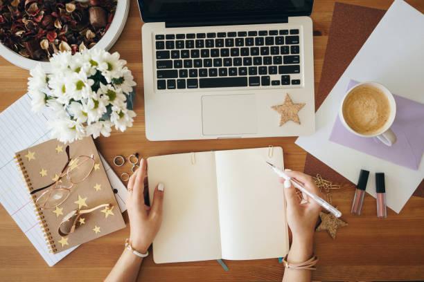 Junge Frau schreibt Notizen und arbeitet an einem Laptop – Foto
