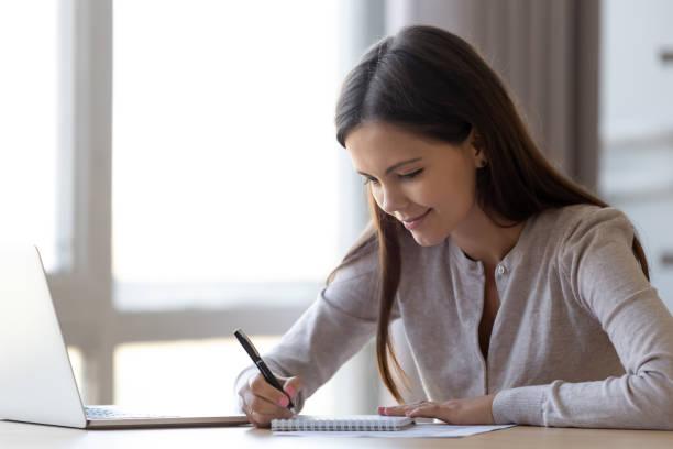 junge frau schreiben von notizen im notizbuch erstellen liste planungsaufgaben - liste stock-fotos und bilder