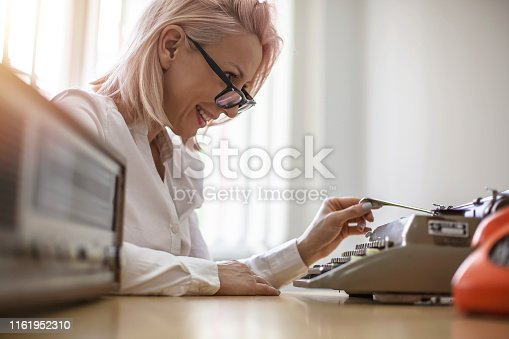 istock Young woman writing on a vintage typewriter 1161952310