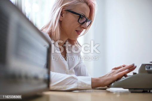 istock Young woman writing on a vintage typewriter 1162038365
