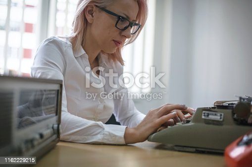 istock Young woman writing on a vintage typewriter 1162229215