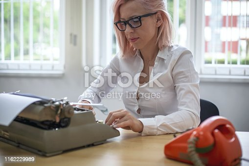 istock Young woman writing on a vintage typewriter 1162229989