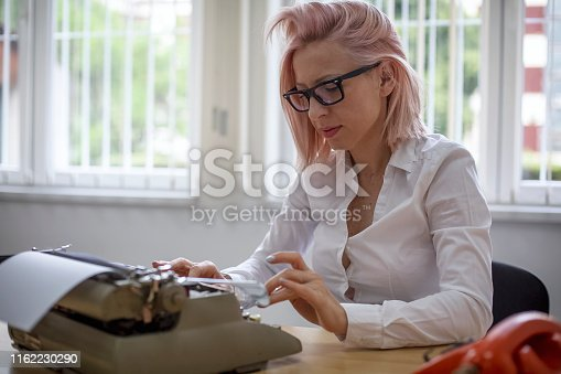 istock Young woman writing on a vintage typewriter 1162230290