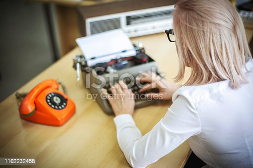 istock Young woman writing on a vintage typewriter 1162232458