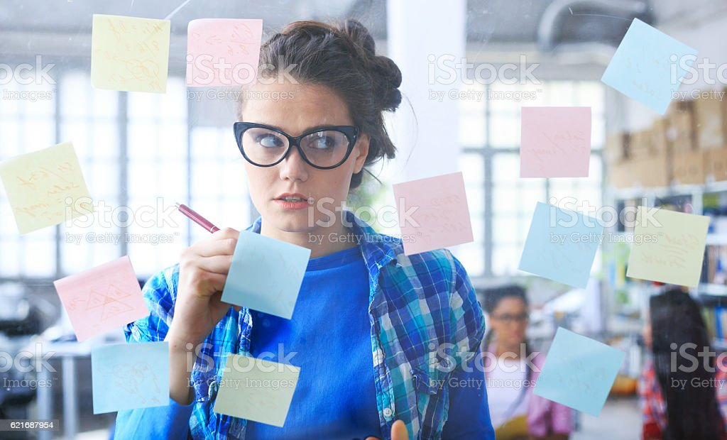 Young woman writing on post-it notes on glass wall stock photo