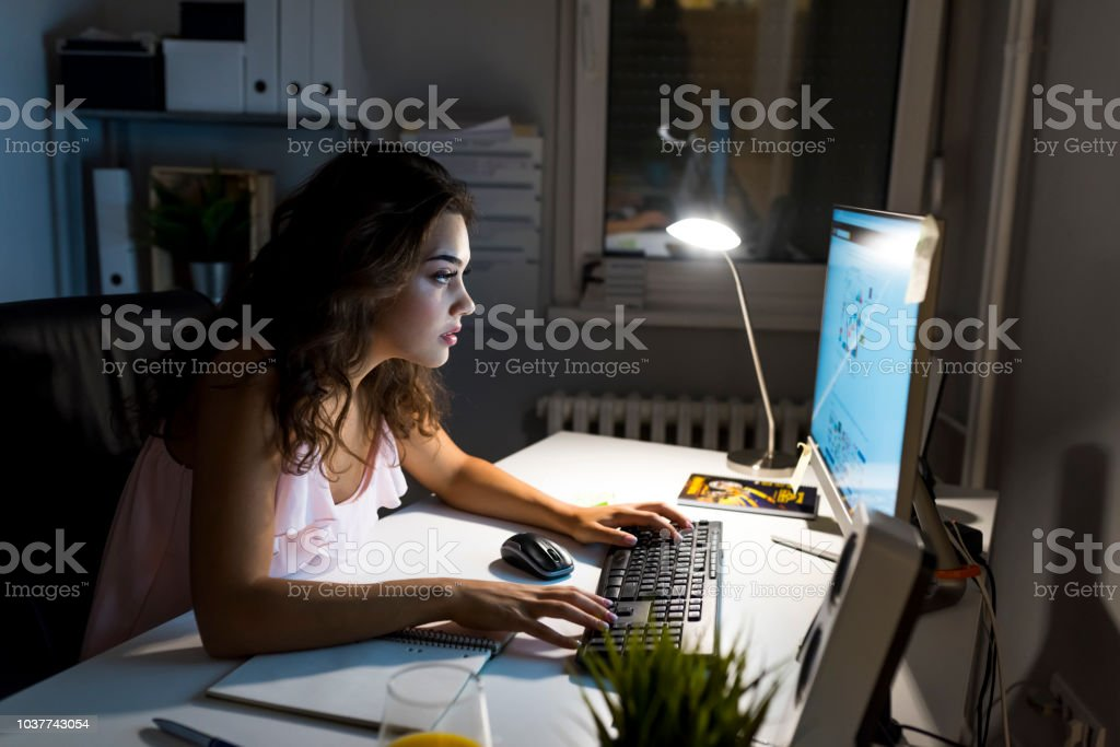 Young woman writing while sitting in her office at night. Woman...