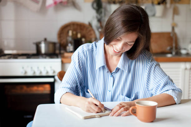 Young woman writting notes in paper notebook. Happy girl sitting at table with cup of coffee stock photo