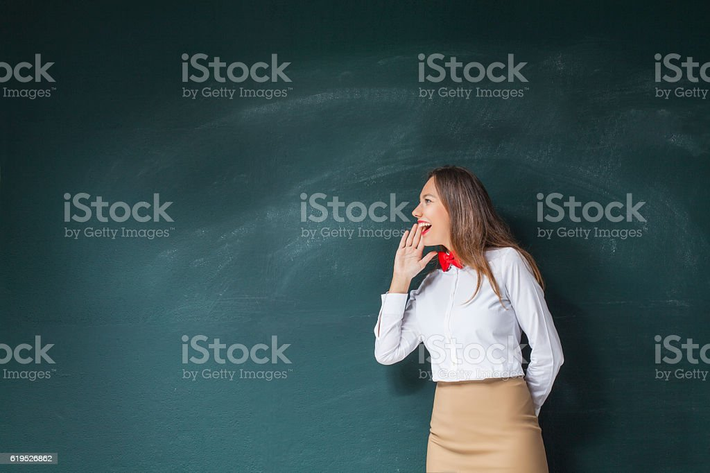 Young woman yelling in front of blackboard stock photo