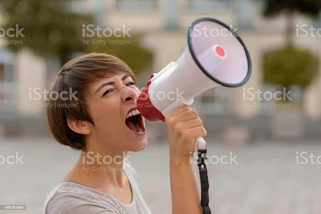 Young woman yelling into a megaphone or bullhorn stock photo