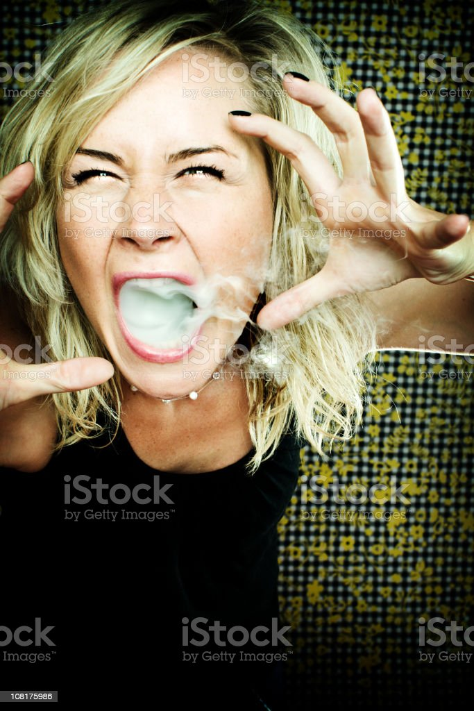 Young Woman Yelling with Smoke Coming from Mouth foto