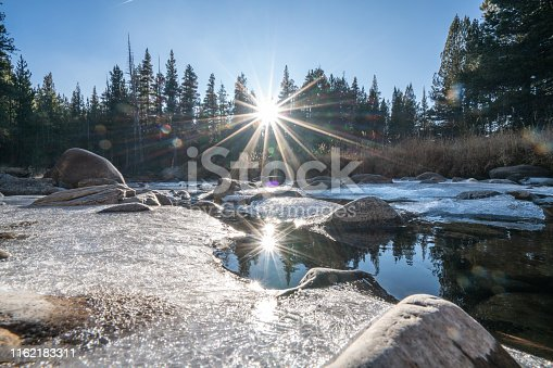 Young woman yoga posing on rock above frozen river in the forest looking at sunset