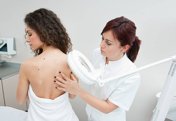 Young woman's back being examined at a dermatologists stock photo
