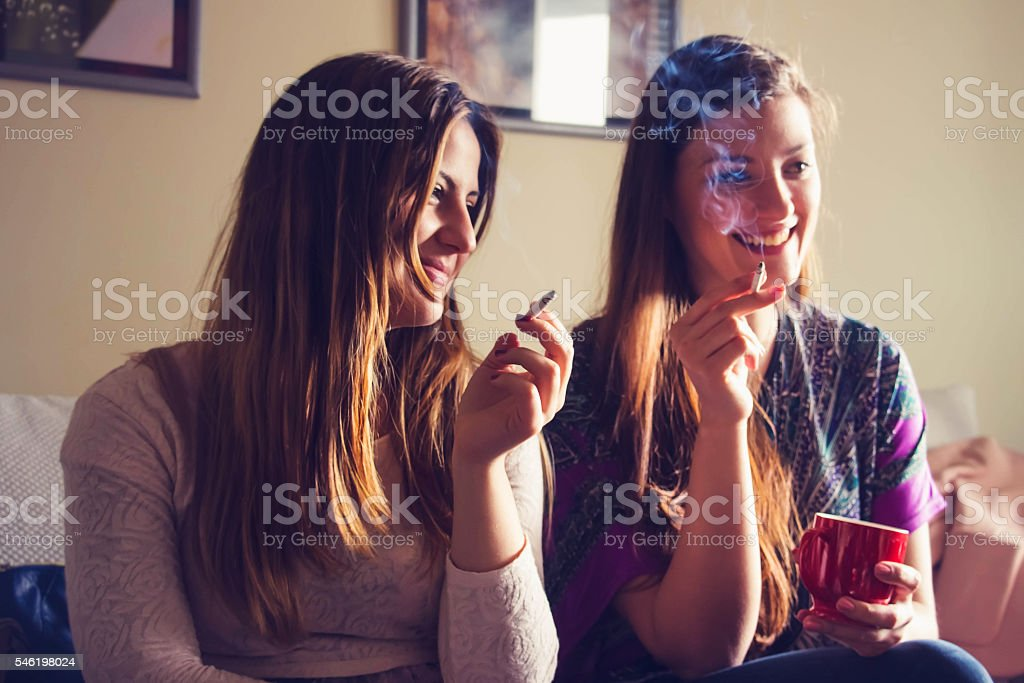 Young womans confronted to cigarettes. Smoke and smilling stock photo