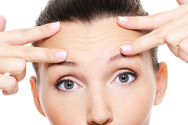 Young woman's face showing wrinkles on forehead Female face with wrinkles on forehead - skincare treatment wrinkled stock pictures, royalty-free photos & images