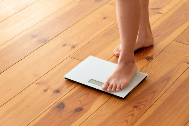 Young woman's feet on wooden floor and weight scale stock photo